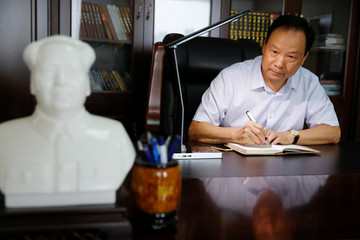 Huayu Hatchery President Wang poses for pictures at a desk in the company's office in Handan
