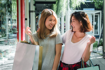 Group of young Asian woman shopping in an outdoor market with shopping bags in their hands. Young Asian women show what they got in shopping bag under warm sunlight. Group outdoor shopping concept.