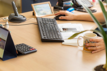 The manager's desk, small depth of field, sharpness on the center of the keyboard, natural light from the window