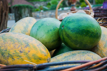 Bright and juicy green and yellow watermelon and melon outdoors on a sunny day