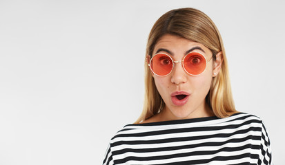 Studio portrait of amazed fascinated young woman in trendy clothes and eyewear expressing full disbelief and astonishment, receiving unexpected positive news, opening mouth and widening eyes