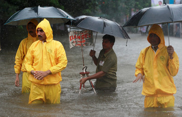 Municipal workers stand next to a choked manhole on a water logged street during heavy rains in Mumbai