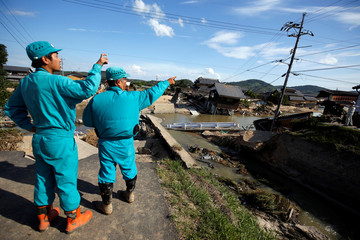 Workers inspect a destroyed bridge and a river bund in a flooded area in Mabi town in Kurashiki