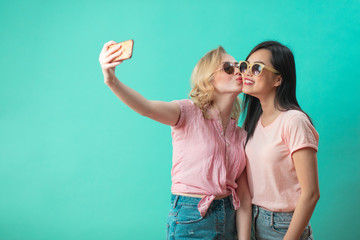 Two diverse young women ethnic friends in summer clothes, wearing sunglasses. Blonde girl kissing her asian friend for fun while making selfie at blue studio background