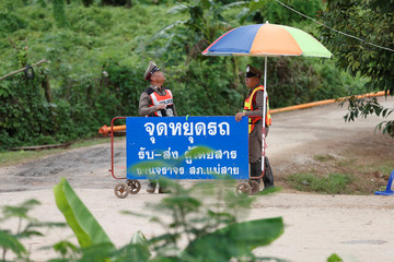 Police stand guard near the Tham Luang cave complex in the northern province of Chiang Rai