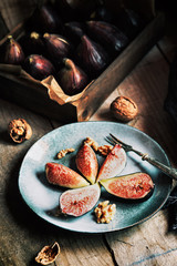 Fresh figs served in a plate with nuts in rustic table