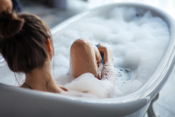 Obraz female massaging her legs with sponge in the tub. back view shot - fototapety do salonu