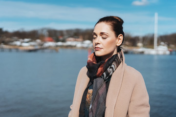 Dreamy woman standing against harbour on sunny day