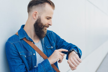 Bearded man looking at his watch