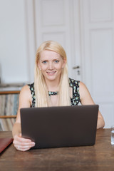 Friendly young blond woman using a laptop computer