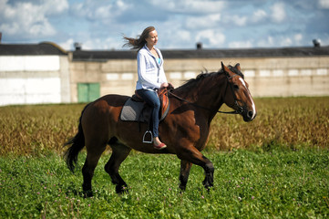 blonde riding a horse in a field