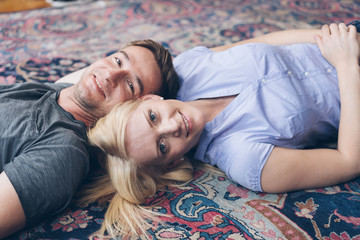 Young couple relaxing head to head on a carpet