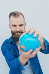 Young smiling bearded man holding globe