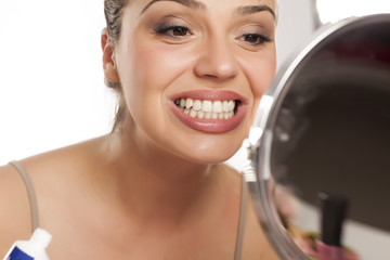 young woman looking her teeth on the mirror