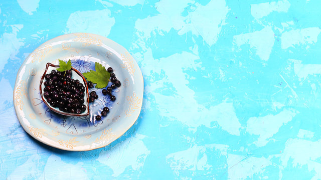 Superfood MAQUI BERRY. Superfoods antioxidant of indian mapuche, Chile. Bowl of fresh maqui berry and maqui berry tree branch on blue background, top view