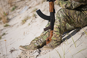 Man in military uniform sits on the sand and holds a rifle with his hands.Selective focus