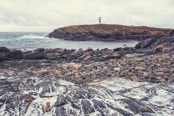 Rocky coast of the Atlantic ocean with lighthouse, severe winter landscape, Lofoten Islands, Norway
