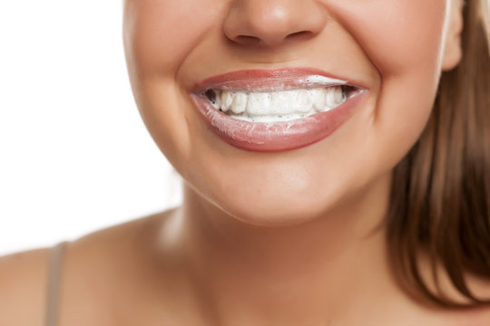 young smiling woman with toothbrush foam on her teeth on white background