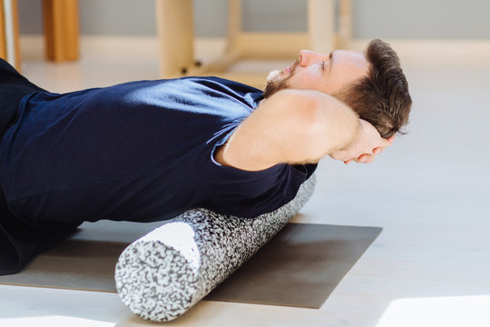 Handsome man performing back exercise on a foam roller being assisted at pilates studio. Patient doing fascia exercise with foam roller on back. Rehabilitation after trauma concept.