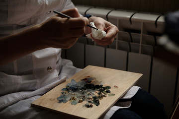 Artist with palette of oil paints. Painter with equipment and colors on workspace. Close up