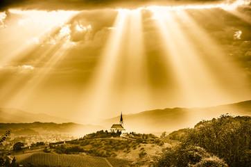 Sun rays shining down on a Church. Sepia color.
