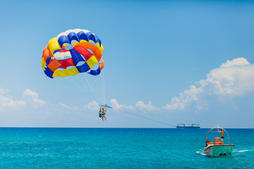 Couple of tourists flying on a colorful parachute