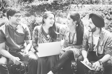 Group of happy young Indian adults using laptop