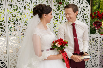 Happy bride and groom looking at each other with love, standing near the ornament wall decorated with flowers.