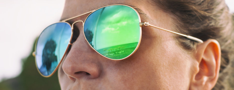 Girl with pilot sunglasses on the beach with reflection, panorama photo