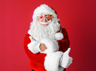 Authentic Santa Claus wearing sunglasses on color background