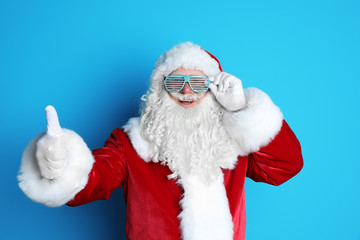 Authentic Santa Claus wearing funny glasses on color background
