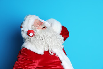 Authentic Santa Claus listening to music on color background
