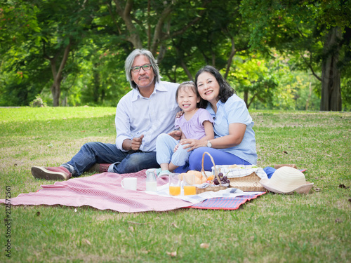 grandparents and grandchild having a picnic in the home garden happy