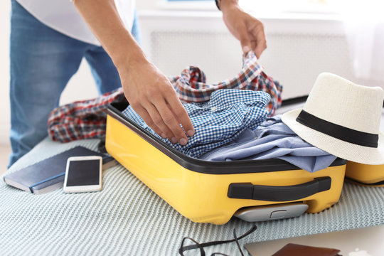 Young man packing suitcase on bed, closeup