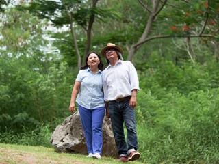 Senior couple walking together in summer park,travel together concept.