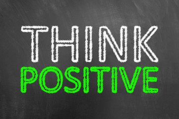 Think positive chalk text on blackboard or chalkboard.
