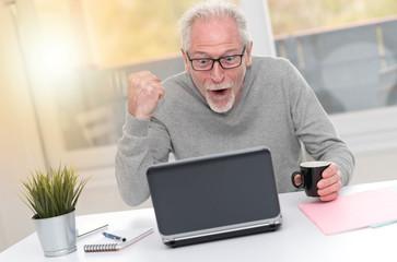 Happy mature man having a good surprise on laptop, light effect