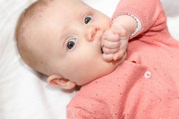 Portrait of cute baby girl with fist in mouth