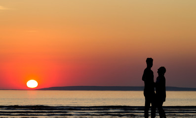 Silhouette of happy couple on the beach at sunset
