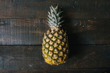 Ripe pineapple on dark wooden background. Tropical fruit creative concept. Shallow deapth  of field.