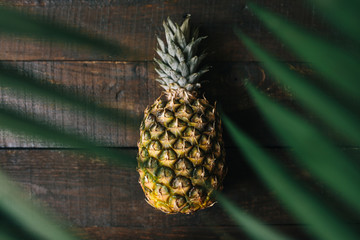 Ripe pineapple, palm leaves frame on dark wooden background. Tropical fruit creative concept.
