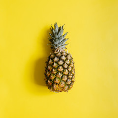 Ripe pineapple on vibrant yellow background isolated. Minimalist style trendy tropical concept. Room for text, copy, lettering.