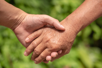Closeup hand of the adult and the old people grasp together.