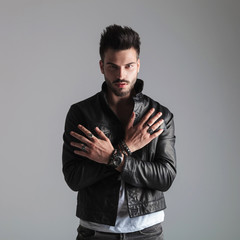 portrait of seductive man in leather jacket showing his rings