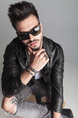 portrait of sexy seated man with sunglasses thinking