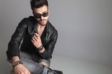 seated man wearing sunglasses and leather jacket looks to side