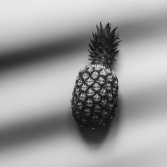 Black and white pineapple fashion trendy exotic fruit concept with shadows. Cinematic film look.