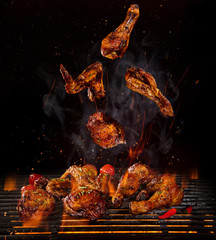 Acrylic Prints Grill / Barbecue Chicken legs and wings on the grill with flames