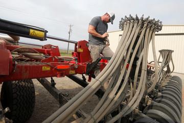 Farmer Blake Davis, 32, works on his fertiliser sprayer in Gideon, Missouri