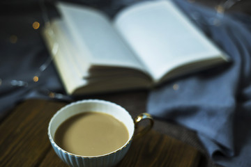 A cup of coffee with milk and a book on cozy domestic plohad. Time for rest in autumn or winter